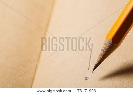Brown notebook, top view. Wooden pencil writing on tne brown paper. Sign. School and education. Student. Writing instruments.
