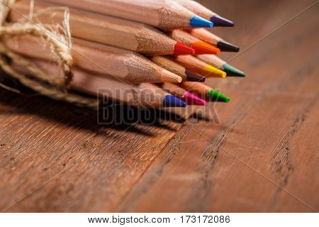 Multicolored pensils decorative rope tied on a wooden table. Back to school. Copy space. Bunch of the colorful pencils. Brown background. Drawing and painting. Art and design.