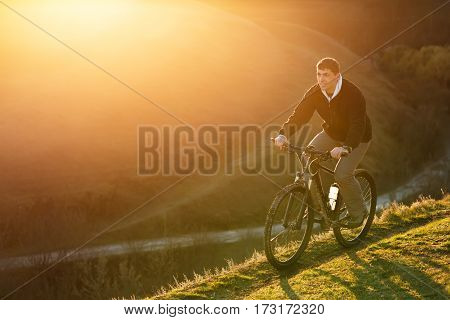 Mountain Bike cyclist riding single track at sunrise, healthy life. Spring landscape with hill and sun. Travel in the countryside. Man in the black jacket.