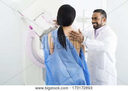 Doctor Assisting Mature Woman Undergoing Mammogram Test