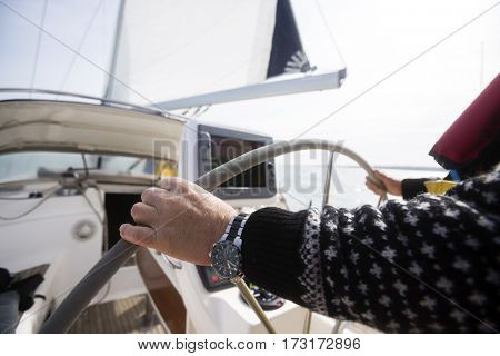 Man's Hands Steering Wheel Of Yacht