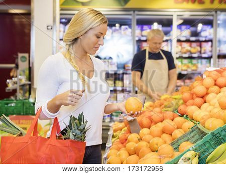 Customer Holding Orange In Grocery Store