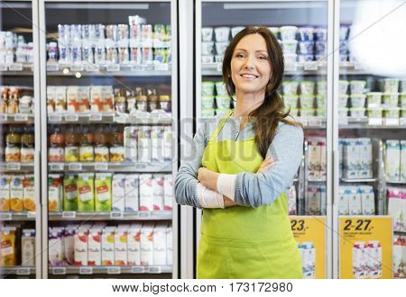 Saleswoman With Arms Crossed Standing Against Refrigerator