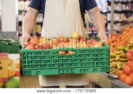 Salesman Carrying Apples In Crate At Grocery Store