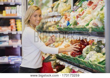 Smiling Woman Buying Capsicum In Supermarket