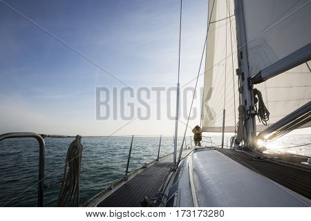 Man Standing On Front Of Yacht Deck In Sea Against Sky