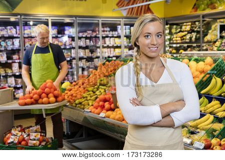 Saleswoman Standing Arms Crossed While Colleague Stacking Orange