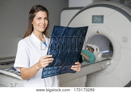 Doctor Holding X-ray While Patient Lying On CT Scan Machine