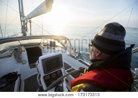 Man Steering Yacht At Helm During Sunset