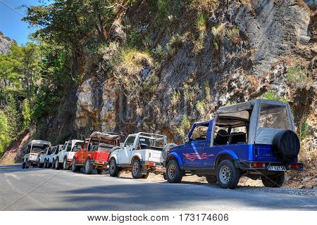 Kemer Antalya Turkey - august 26 2014: Jeep safaris on the mountain roads in the vicinity of Kemer a lot of jeeps parked on the roadside.