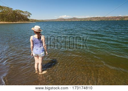 One girl stand on lagoon water in colorful panorama landscape. Woman standing in masaya lagoon