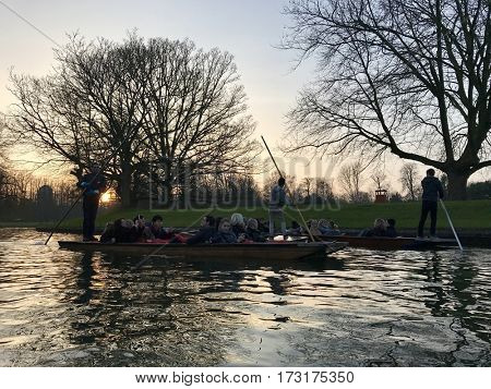 CAMBRIDGE - FEBRUARY 18, 2017: Tourists and guides Punting along The Backs on the River Cam at sunset on a winters evening in Cambridge, Cambridgeshire, UK.