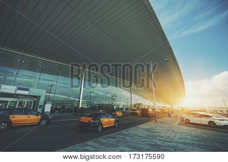 Cabstand in front of modern airport doors in Barcelona cabrank with a lot of taxies near windowed facade of contemporary Airport terminal in Spain with road long ceiling and parking lot