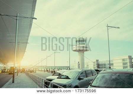 Parking lot and road near modern contemporary airport terminal in front of air traffic control tower with many passengers and staff passing in distance Barcelona Spain