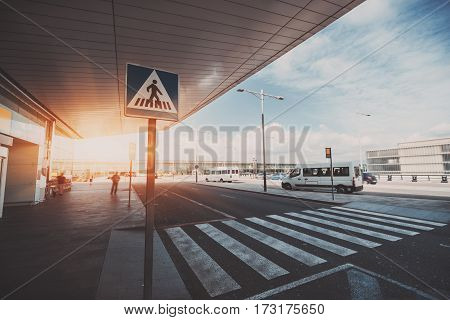 Pedestrian crossing next to contemporary modern airport terminal entrance zebra traffic cross way with road sing with parking lot and small buses in distance on sunny day in Barcelona Spain