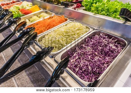 Salad bar with vegetables in silver trays in the restaurant healthy food. Select focus