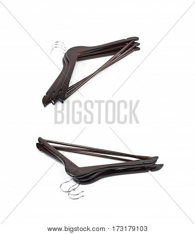 Pile of dark wooden hangers isolated over the white background, set of two different foreshortenings
