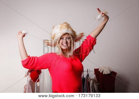 Outfit for cold days ideas fashion and clothing concept. Attractive smiling blonde woman in wardrobe picking clothes wearing furry winter hat