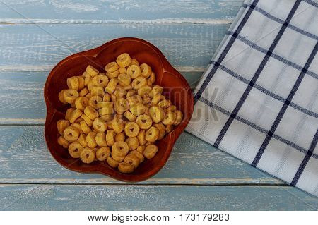 Corn flakes in wicker basket and scattered flakes on wooden table