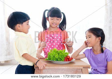 Lovely Asian kids preparing salad at home