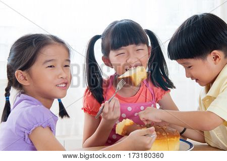 Lovely Asian kids eating home baked cake