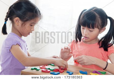Lovely Asian kids playing alphabet letters together