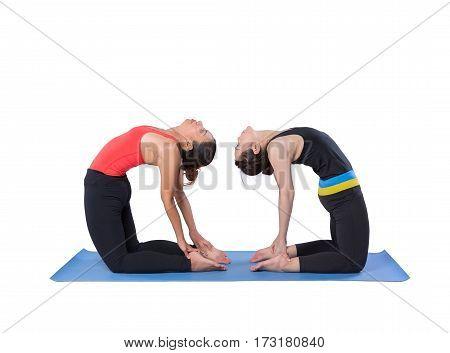 Two young women doing yoga asana camel pose.