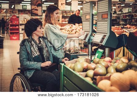 Young girl helping her disabled mothter in wheelchair in a grocery store