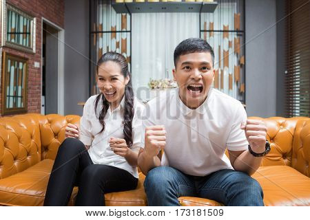 Asian Couple having fun watching soccer game
