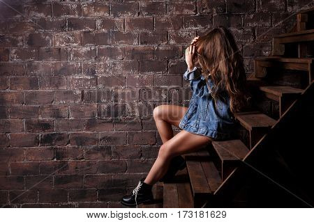 Young sexy girl in a denim jacket sits on the steps to the loft room.