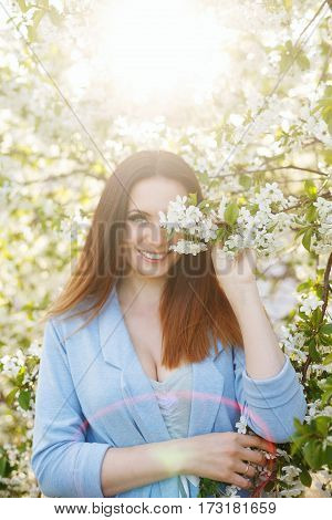 Cute attractive girl in blossoming apple trees. Spring mood.