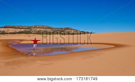 Man hiker wading in little lake. Coral Pink Sand Dunes State Park. Kanab. Cedar City. Utah. United States.