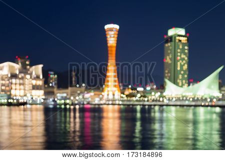 Blurred light at twilight Kobe port tower with water reflection abstact background