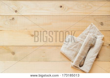 top view of one vintage fork on a linen fabric on wooden boards background with copy negative space
