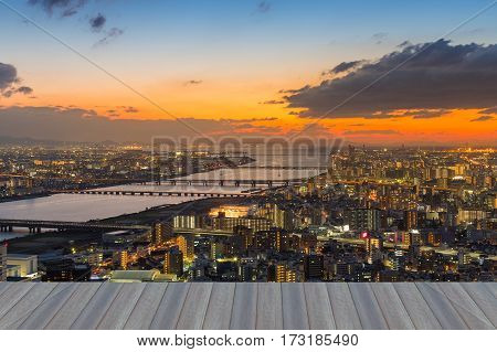 Opening wooden floor beautiful after sunset sky over Osaka city central business downtown Japan