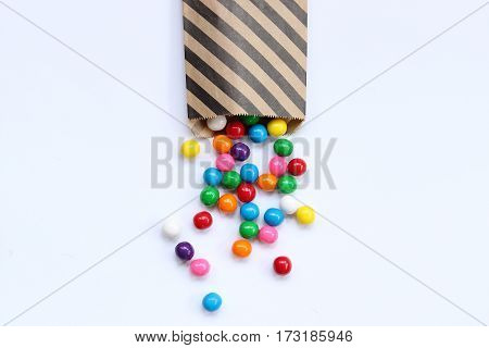Bright, colorful gumballs spill out of striped treat bag onto white open space for copy.
