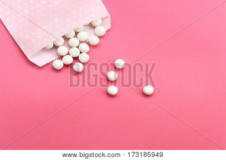 White gumballs spill out of pink polka dot bag onto pink background with open space for copy.