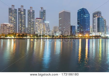 Night office building with water reflection at twilight cityscape background