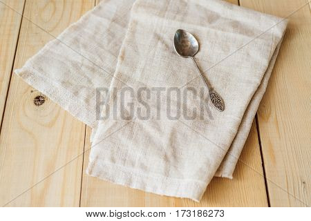 view from angle above of one vintage spoon on a linen fabric on wooden boards background with copy negative space