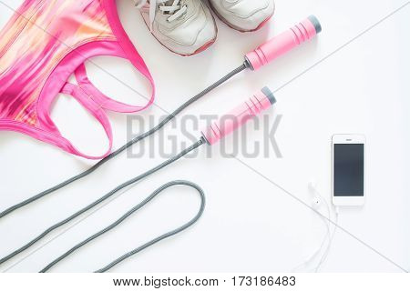 Flat lay of sport items in pink concept with mobile device isolated on white background