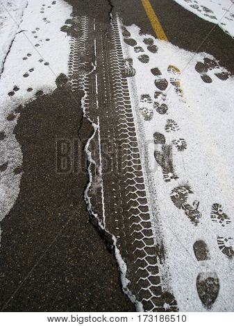 Snow Tracks of tires and shoes on a city path