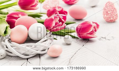 Easter decoration with eggs and spring flowers on wood background