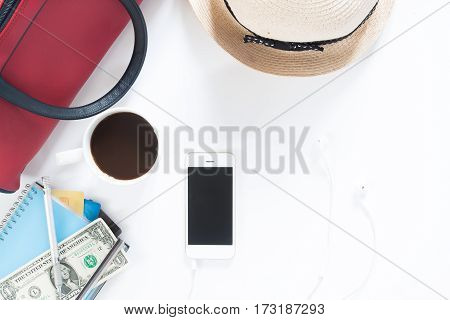 Flat lay of mobile device money credit card hand bag and coffee Travel and lifestyle concept top view