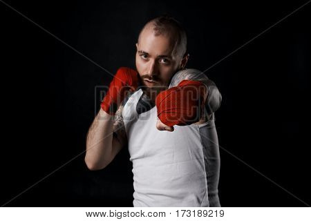 Close-up of hand of boxer ready for a fight. Strong arms with red bandage on fists. Kick boxing concept. Brutal man portrait in white t-shirt with copy space on black background.