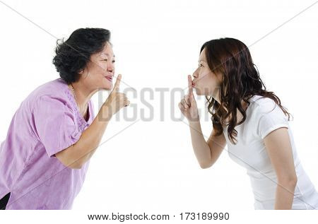 Portrait of Asian adult daughter and her senior mother gesturing quiet sign, finger on lips, isolated on white background.