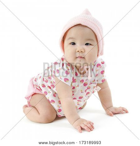 Portrait of full length cute Asian baby girl in pink clothes crawling on floor, isolated on white background.