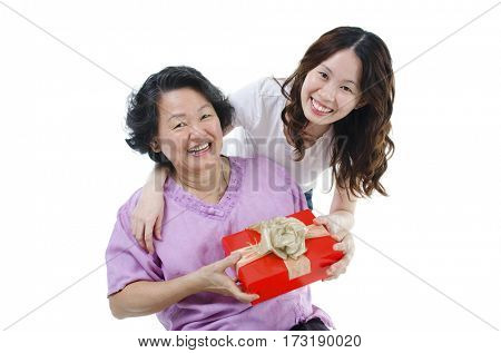 Celebrating mothers day or birthday. Portrait of Asian senior parent getting a gift box from adult daughter, isolated on white background.