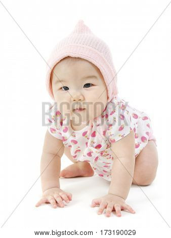 Portrait of full length adorable Asian baby girl in pink clothes crawling on floor, isolated on white background.
