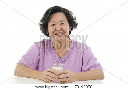 Portrait of happy Asian senior adult woman hand holding a glass soy milk, isolated on white background.
