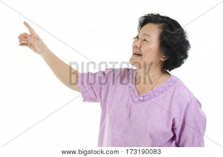 Portrait of Asian senior adult woman smiling and hand pointing at blank copy space, isolated on white background.